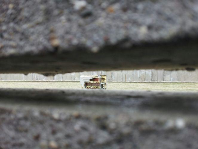 Desde el muro pequeño, el primer obstáculo para pasar. Entre la rendija de los bloques de cemento se ve el último muro, que parece que esta cerca... pero entre uno y otro, esta el alumbrado, los guardas y los clavos.